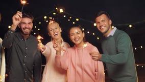 Счастливые друзья с бенгальскими огнями на партии крыши сток-видео