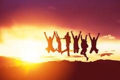 Счастливые друзья silhouettes заход солнца скачек стоковые фото