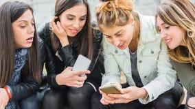 Счастливые 4 друз используя мобильные телефоны на скамейке в парке Стоковая Фотография