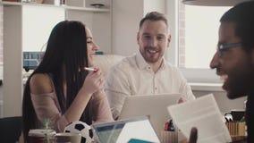 Счастливые европейские бизнесмены усмехаются жизнерадостно на таблице офиса, обсуждая работу с многонациональным замедленным движ видеоматериал