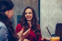 Счастливые женские друзья говоря и выпивая кофе пока смотрящ каждое в кафе стоковое фото rf