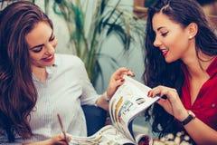 Счастливые женские друзья говоря и читая журнал в кафе стоковое фото