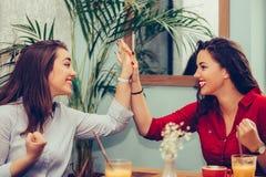 Счастливые женские друзья дают высоко, празднующ успех пока смотрящ один другого стоковая фотография rf