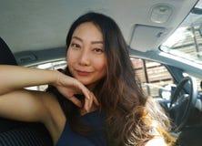 Счастливые женские друзья играя и имея потеху в зеленой траве Портрет красивой азиатской женщины сидя в автомобиле и усмехаться стоковое фото