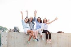 Счастливые женские друзья имея потеху на выходных, на пикнике Outdoors Молодые усмехаясь девушки студента сидя на конкретной гран стоковое изображение rf
