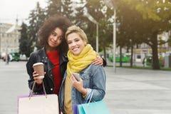 Счастливые женские друзья с хозяйственными сумками outdoors Стоковое фото RF