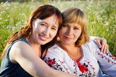 Счастливые женщины говоря и смеясь над в природе с зеленой предпосылкой Стоковая Фотография