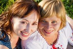 Счастливые женщины говоря и смеясь над в природе с зеленой предпосылкой Стоковые Изображения RF