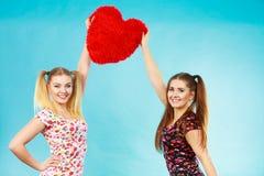 Счастливые 2 женщины держа подушку сердца форменную Стоковые Фотографии RF