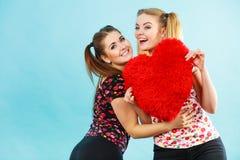 Счастливые 2 женщины держа подушку сердца форменную Стоковое Фото