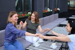 Счастливые женщины держа руки приближают к чашкам кофе на кафе Стоковое фото RF