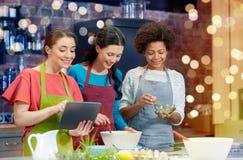 Счастливые женщины с ПК таблетки варя в кухне Стоковые Фото