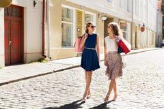 Счастливые женщины с хозяйственными сумками идя в город Стоковая Фотография RF
