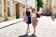 Счастливые женщины с хозяйственными сумками идя в город Стоковая Фотография