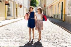 Счастливые женщины с хозяйственными сумками идя в город Стоковое Изображение