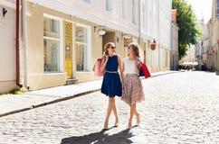 Счастливые женщины с хозяйственными сумками идя в город Стоковое фото RF