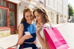 Счастливые женщины с хозяйственными сумками и smartphone Стоковые Изображения RF