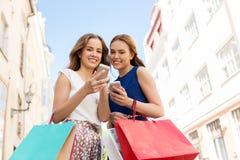 Счастливые женщины с хозяйственными сумками и smartphones Стоковое Фото