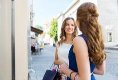 Счастливые женщины с хозяйственными сумками на внешней витрине магазина Стоковая Фотография
