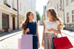 Счастливые женщины с хозяйственными сумками на улице города Стоковые Фотографии RF