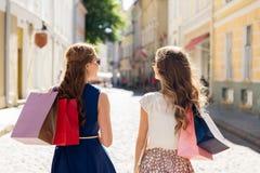 Счастливые женщины с хозяйственными сумками на улице города Стоковые Изображения RF