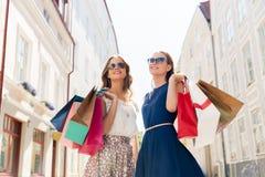 Счастливые женщины с хозяйственными сумками на улице города Стоковые Изображения