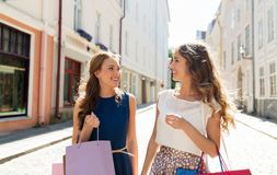 Счастливые женщины с хозяйственными сумками на улице города Стоковая Фотография RF