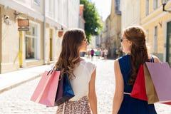 Счастливые женщины с хозяйственными сумками на улице города Стоковые Фото