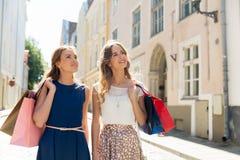 Счастливые женщины с хозяйственными сумками на улице города Стоковое Фото
