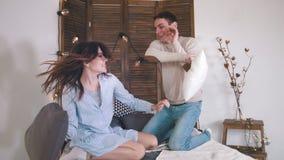 Счастливые жизнерадостные любящие пары имея бой в кровати, девушке щекоча парня стоковая фотография