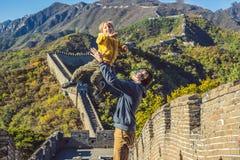 Счастливые жизнерадостные радостные туристы папа и сын на Великой Китайской Стене Китая имея потеху на смеяться перемещения усмех стоковое фото