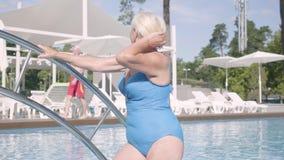Счастливые зрелые пары ослабляя на бассейне в гостиничном комплексе совместно Привлекательная старшая женщина загорая и развевая видеоматериал