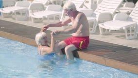 Счастливые зрелые пары ослабляя на бассейне в гостиничном комплексе совместно Старший человек сидя на краю удерживания бассейна сток-видео