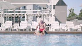 Счастливые зрелые пары ослабляя на бассейне в гостиничном комплексе совместно Милый старший человек сидя на краю бассейна видеоматериал