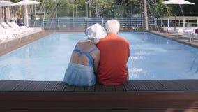 Счастливые зрелые пары сидя на краю бассейна Милый старший человек и женщина ослабляя в гостиничном комплексе t акции видеоматериалы