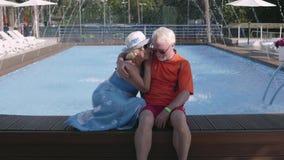 Счастливые зрелые пары сидя на краю бассейна Милый старший человек и женщина ослабляя в гостиничном комплексе t видеоматериал