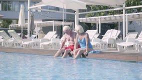 Счастливые зрелые пары сидя на краю бассейна с их ногами в воде Милый старший человек и женщина ослабляя внутри сток-видео