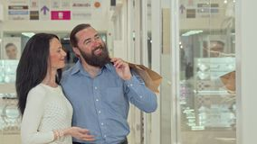 Счастливые зрелые пары смотря витрину магазина одежды на торговом центре акции видеоматериалы