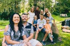Счастливые зрелые пары с 9 детьми в парке Стоковые Изображения