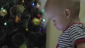 Счастливые игра и взгляд ребенка на планшете около рождественской елки на внутреннем доме Xmas ночи акции видеоматериалы