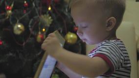 Счастливые игра и взгляд ребенка на планшете около рождественской елки на внутреннем доме Xmas ночи видеоматериал