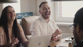 Счастливые кавказские бизнесмены усмехаются и смеются над на многонациональной встрече офиса в coworking замедленным движением та акции видеоматериалы