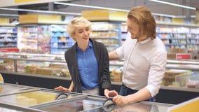 Счастливые кавказские пары выбирают замороженную еду от холодильника супермаркета сток-видео