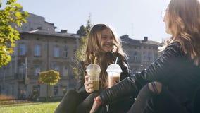 Счастливые кавказские ученицы колледжа сидя на лужайке во время перерыва пока коктейли и что-то питьевого молока говоря акции видеоматериалы