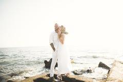 Счастливые как раз пожененные молодые пары свадьбы празднуя и имеют потеху на красивом заходе солнца пляжа стоковая фотография rf