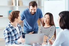 Счастливые 4 коллеги думая над планом Стоковое Изображение RF