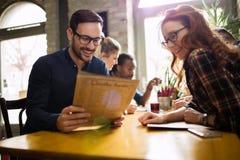 Счастливые коллеги от работы общаясь в ресторане Стоковое фото RF