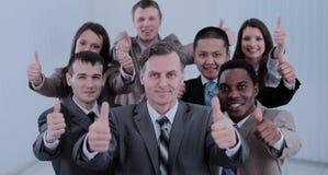 Счастливые коллеги показывая большие пальцы руки вверх в их офисе Стоковые Изображения
