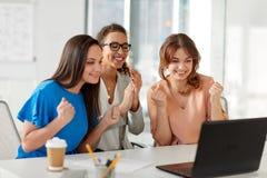 Счастливые коммерсантки с компьтер-книжкой на офисе Стоковое Фото