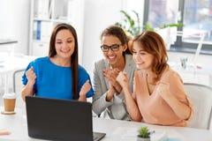 Счастливые коммерсантки с компьтер-книжкой на офисе Стоковое Изображение RF